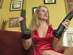 Sarah James in red lingerie holding two huge dildo