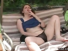 Redhead bitch masturbates while smoking on swing
