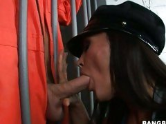 Seductive Lisa Ann doing a blowjob on a jail, dressed as a police-woman.