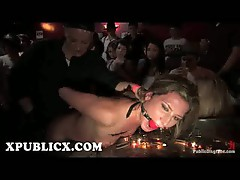 Gagged Ariel X fucked with strap on toy in lesbian bar