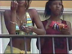 Black lesbians kissing on hotel balcony