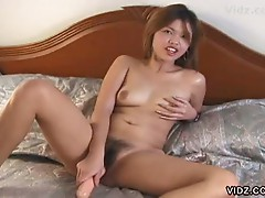 Asian bitch stuffs hairy slit with toy
