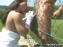 Hot brunette sucking two cock that are behind a fence