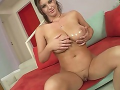 Horny bitch oiling her boobs and showing them for the camera