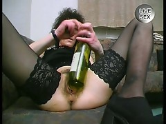 A bottle of wine inserted n mature lady's pussy