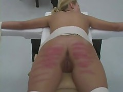 Young women are strapped to a table and caned
