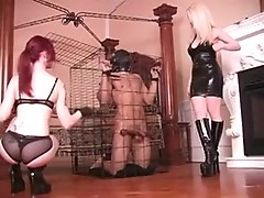 A man is put into cage and derided over by two ravenous mistresses